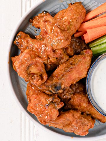 chicken wings on a plate with carrot and celery sticks and blue cheese dip