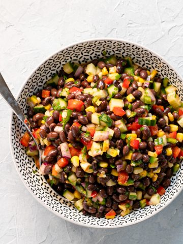 black bean salad in a black and white bowl with spoon on light grey background