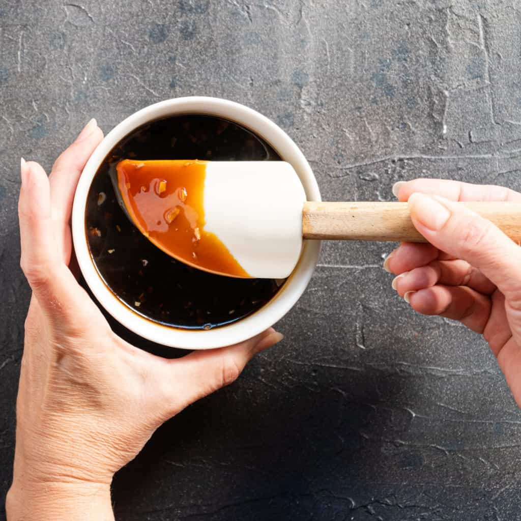 teriyaki sauce in a white bowl with white rubber spatula held in hands