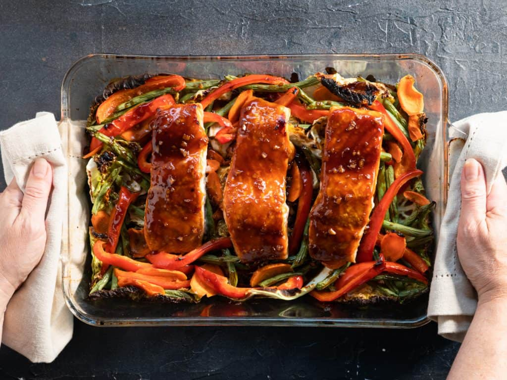 3 salmon filets with teriyaki sauce on top of vegetables. Just out of the oven in a glass dish