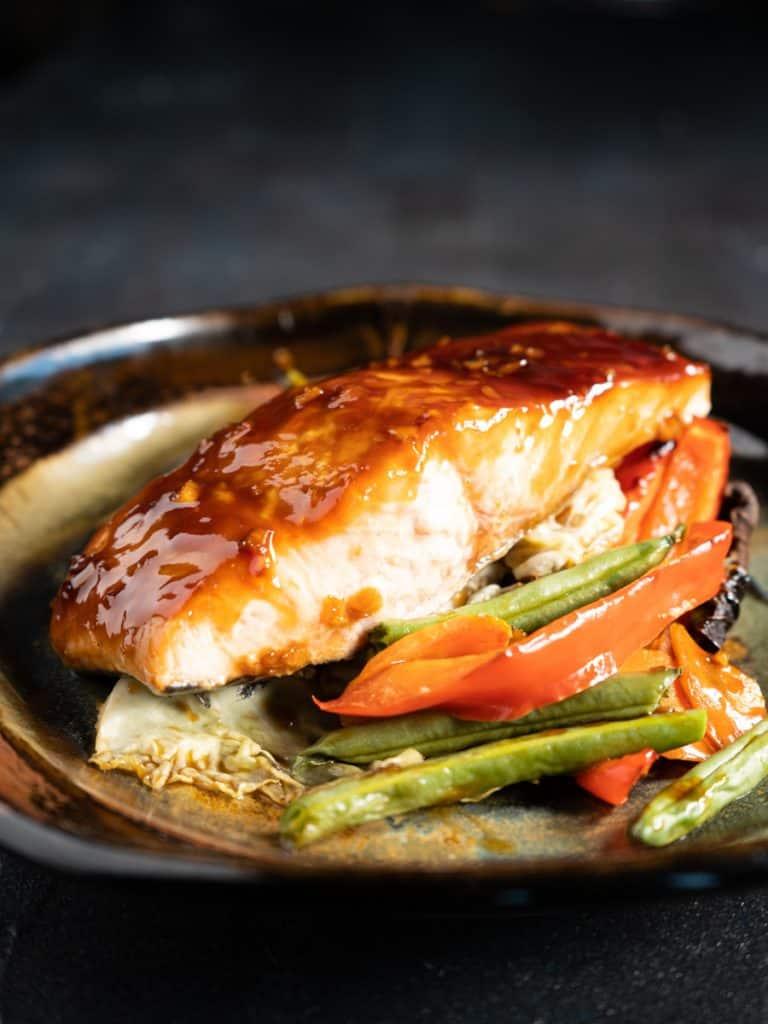 teriyaki salmon filet on a pile of vegetables