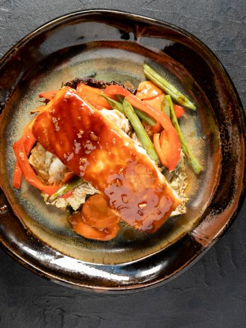 Salmon and vegetables on brown pottery plate