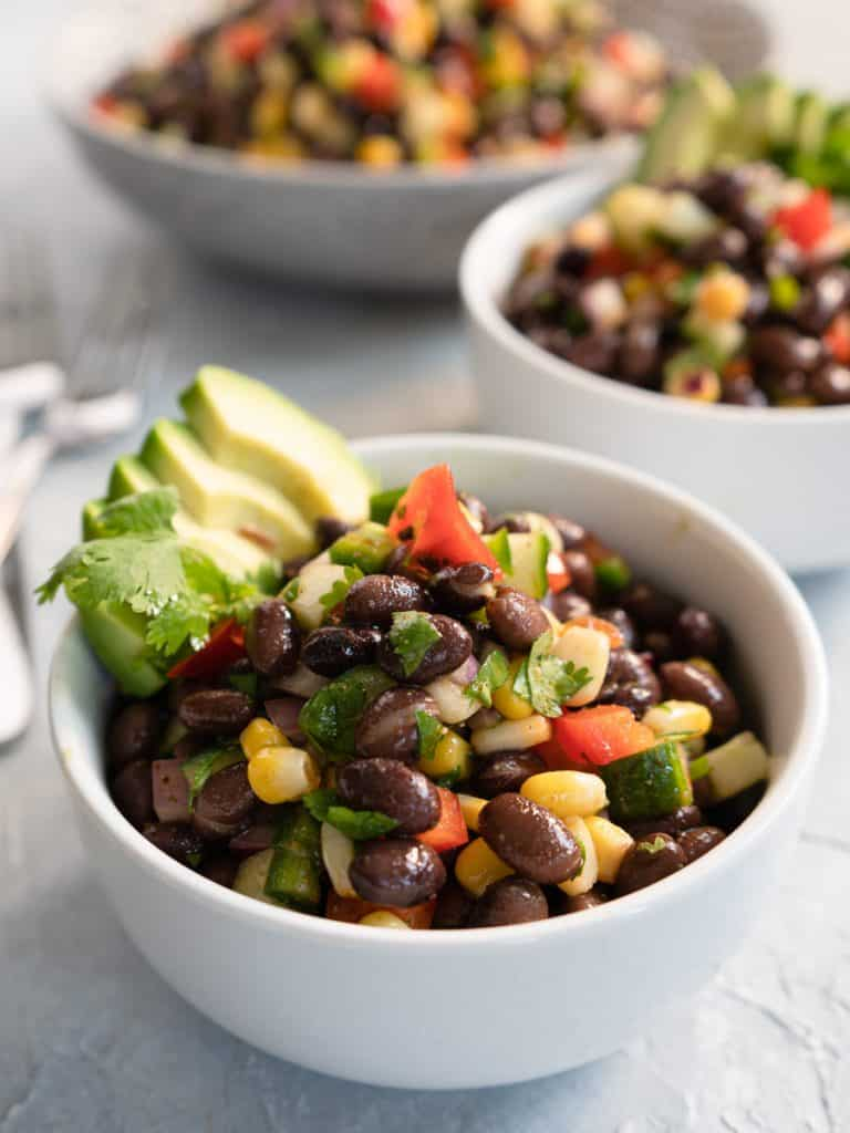 Close up of a white bowl of tex-mex black bean salad with 2 bowls in the background. Garnished with avocado slices
