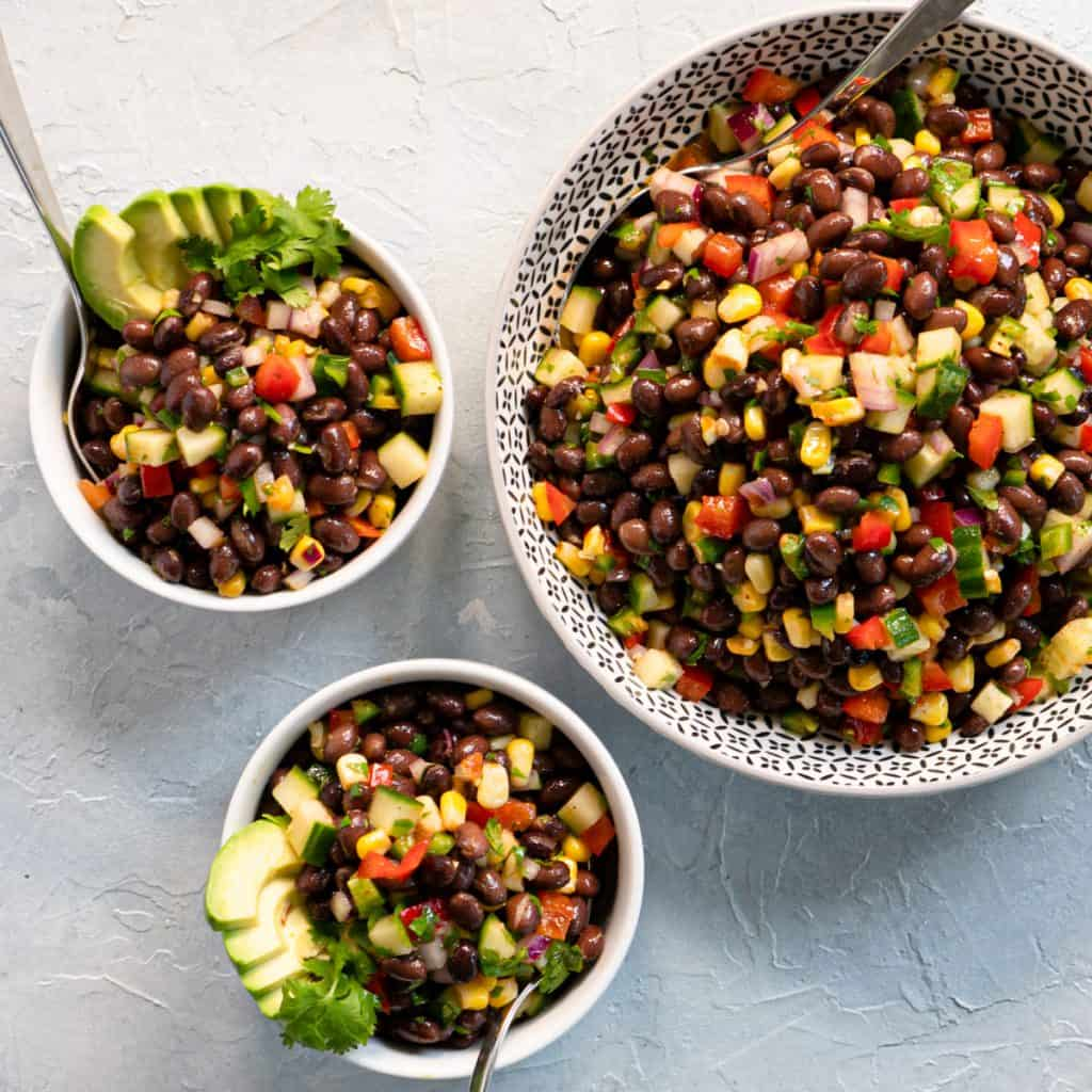 Tex-mex black bean salad in serving bowl with two individual bowls. Garnished with sliced avocado