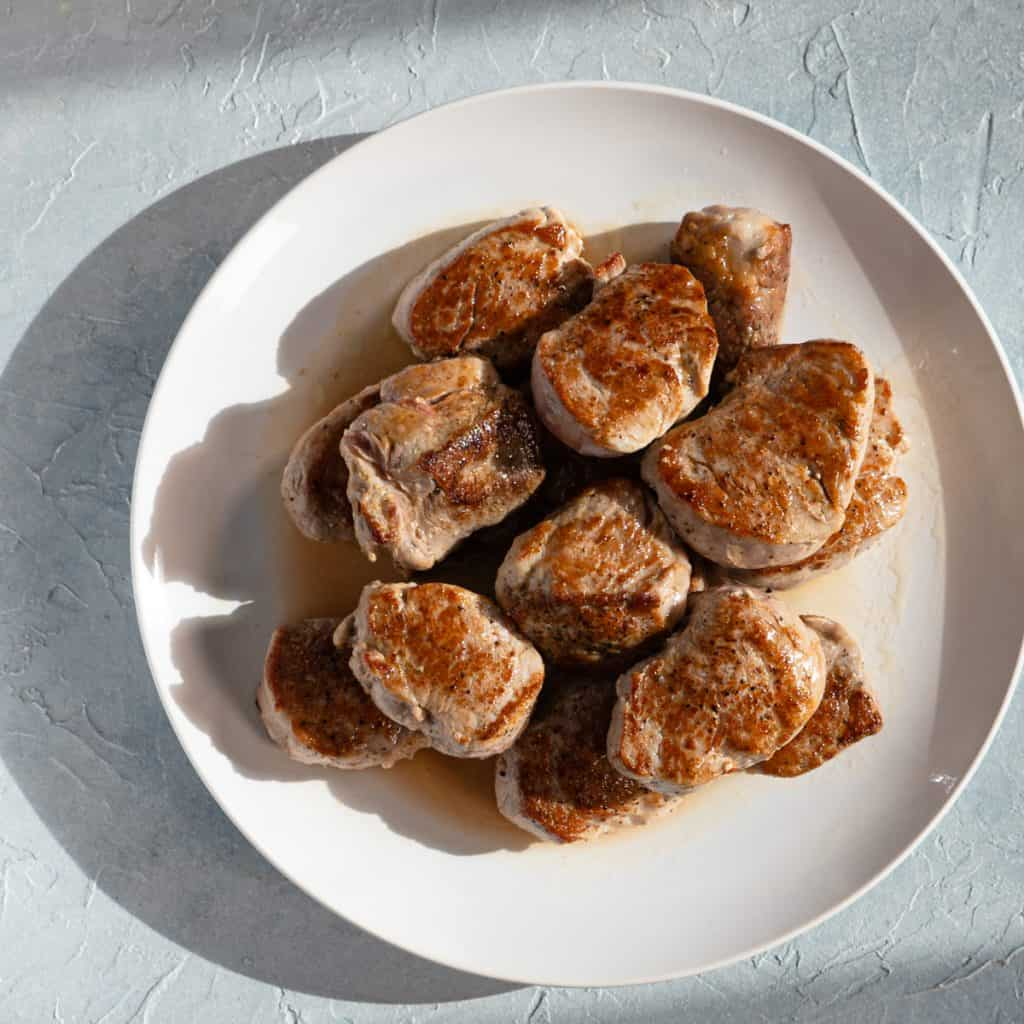 seared pork medallions on a white plate
