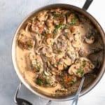 pork medallions in creamy mushroom sauce in pan with spoon