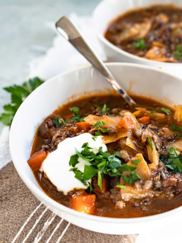 cabbage roll soup in white bowl topped with sour cream and fresh parsley