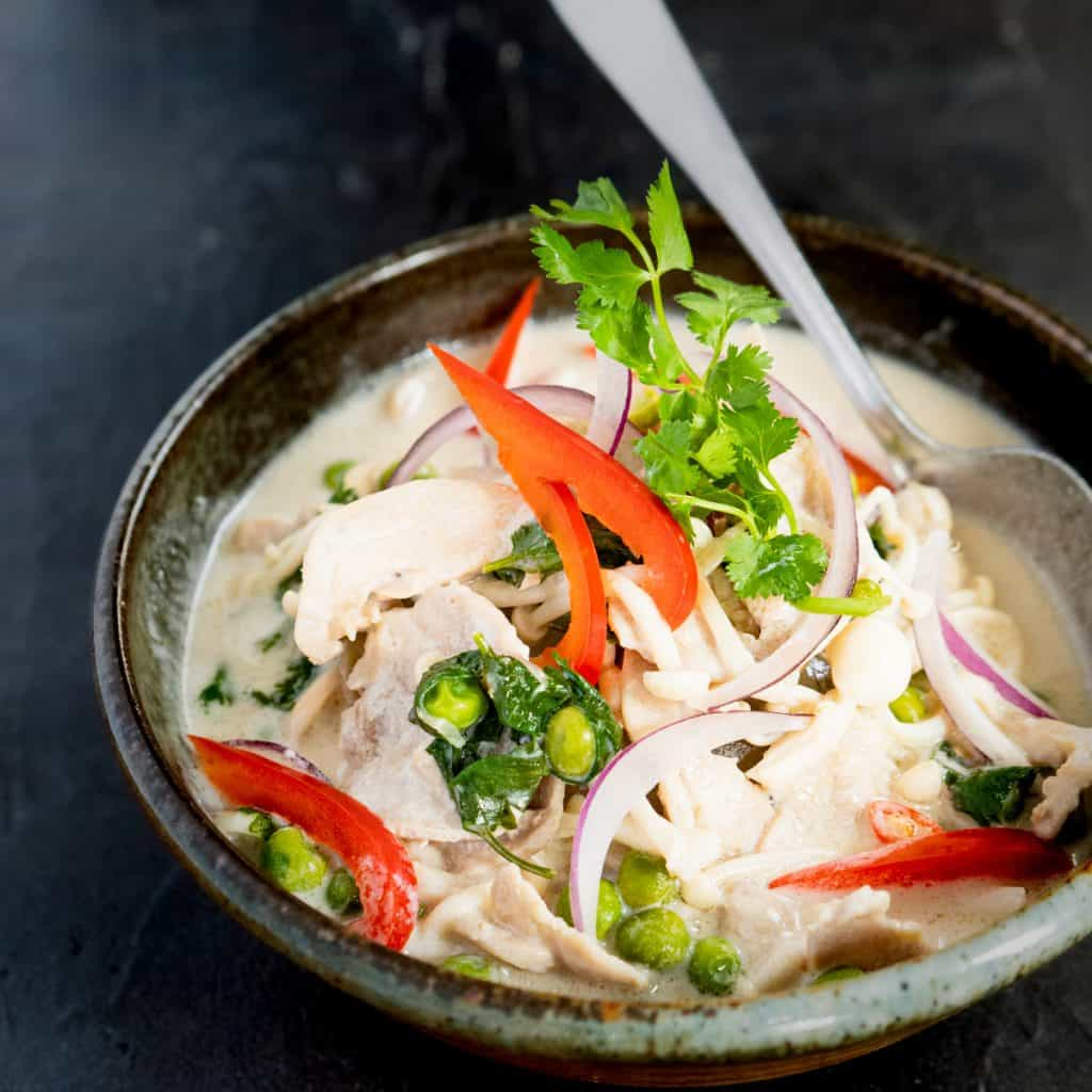 thai style coconut chicken soup in ceramic bowl
