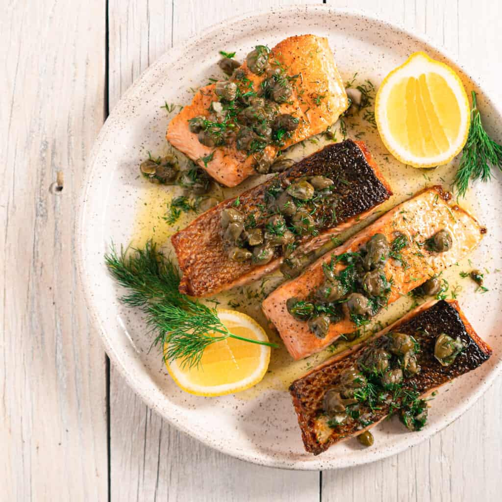 four fillets of Pan seared salmon with fried caper vinaigrette on a white ceramic plate, garnished with fresh dill and lemon