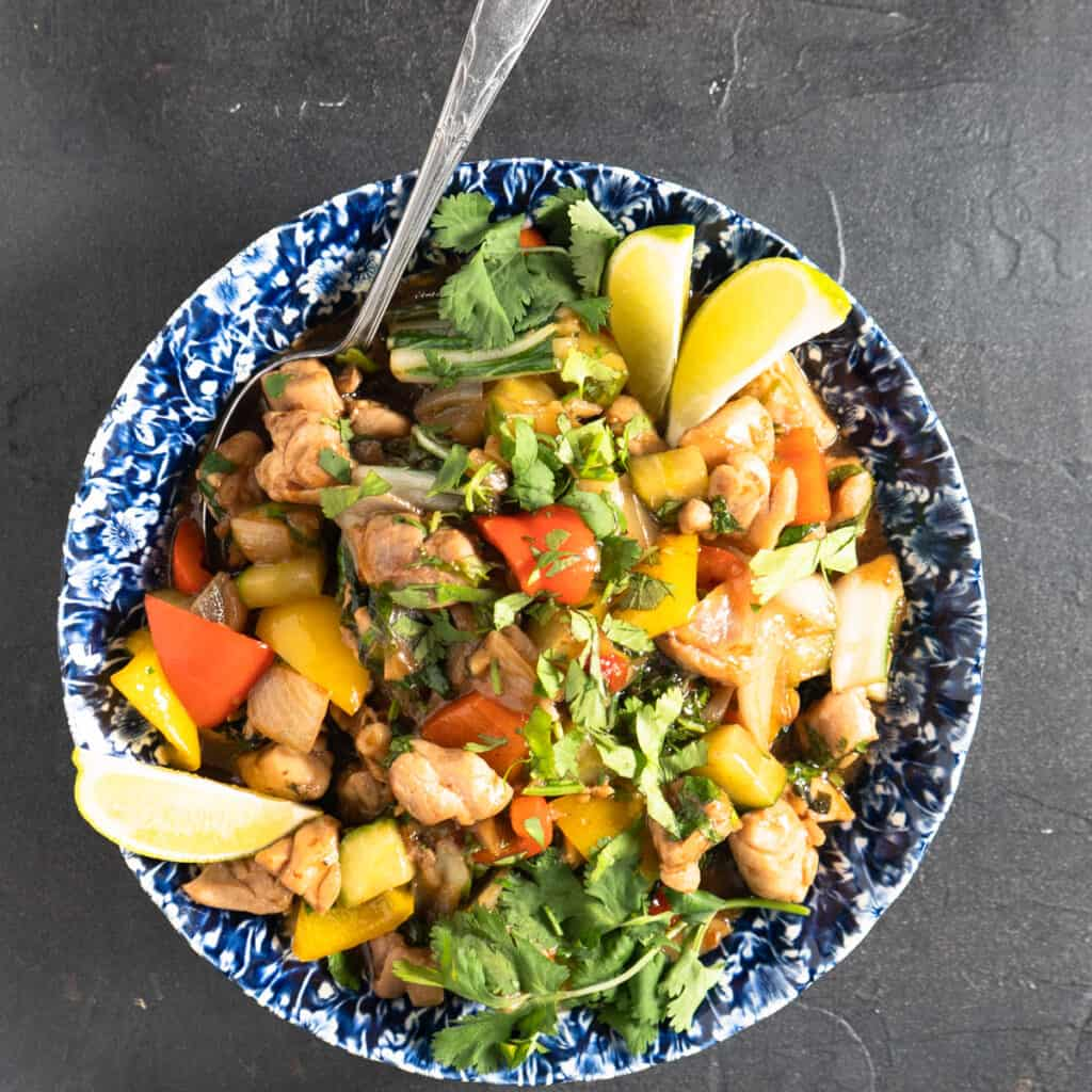 Thai style chicken stir fry in blue and white bowl with spoon. Garnished with fresh lime and cilantro