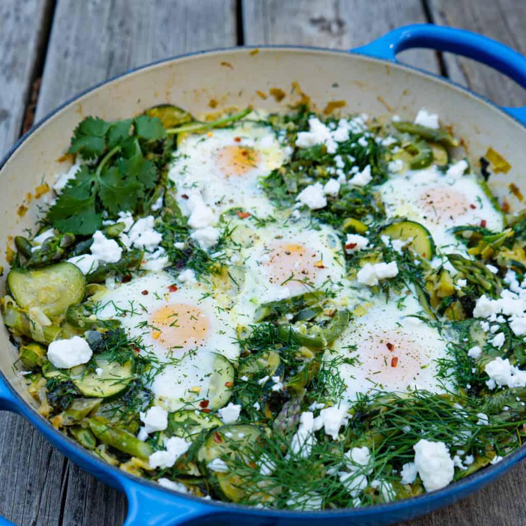 Green shakshuka in a blue casserole on wood background